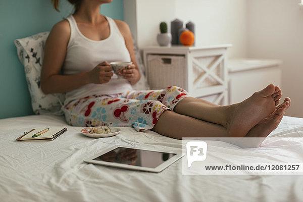 Frau sitzt auf dem Bett neben der Tablette und trinkt Kaffee.