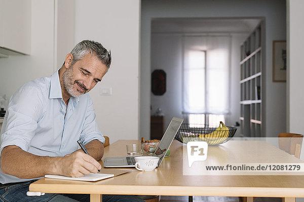 Lächelnder Mann beim Schreiben im Notebook und Laptop im Home-Office