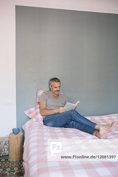 Erwachsener Mann sitzt zu Hause auf dem Bett und liest das Buch.