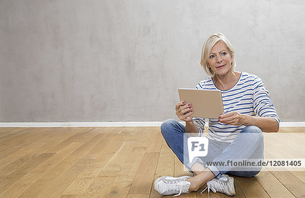 Portrait of smiling senior woman with tablet sitting on the floor