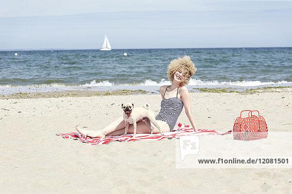 Fröhliche junge Frau entspannt sich mit ihrem Hund am Strand