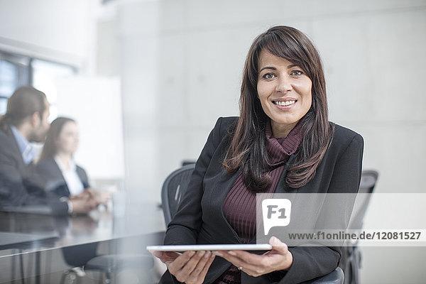 Porträt einer lächelnden Geschäftsfrau mit Tablette auf einer Besprechung im Konferenzraum