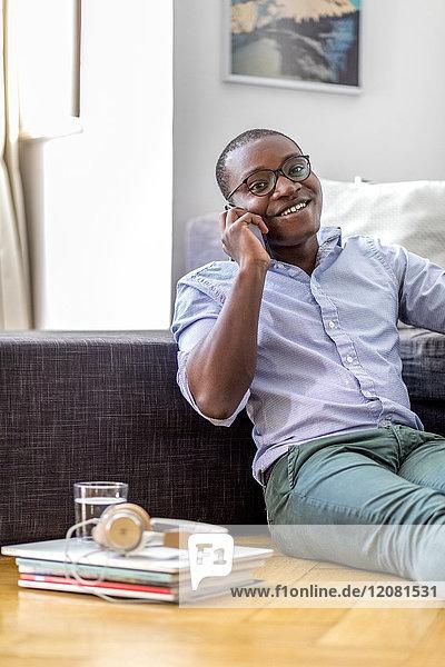 Lächelnder junger Mann am Telefon  der auf dem Boden im Wohnzimmer sitzt.