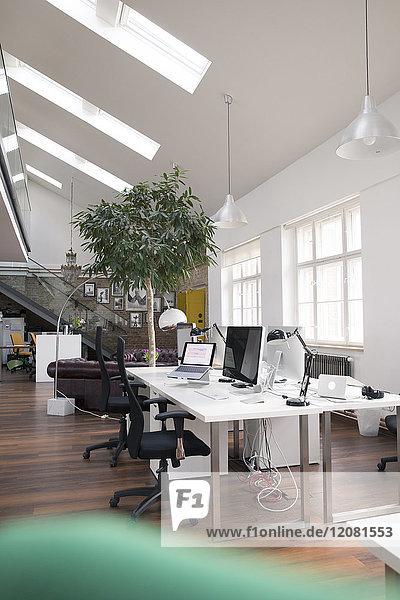 Schreibtische mit PCs im hellen und modernen Großraumbüro