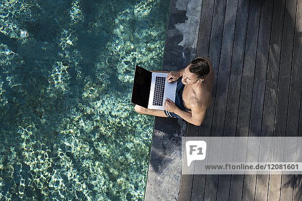 Erwachsener Mann  der am Pool sitzt und den Laptop benutzt.
