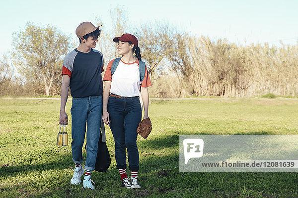 Lächelndes junges Paar mit Baseballausrüstung beim Spaziergang im Park