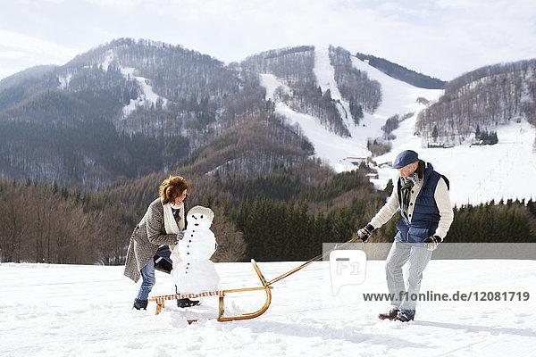 Seniorenpaar mit Schneemann auf Schlitten in Winterlandschaft