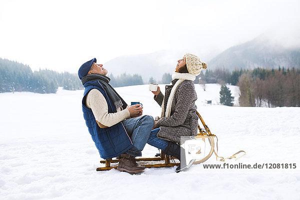 Seniorenpaar auf Schlitten sitzend mit heißen Getränken in verschneiter Winterlandschaft nach oben schauend