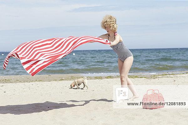 Junge Frau mit blasendem Strandtuch am Meer