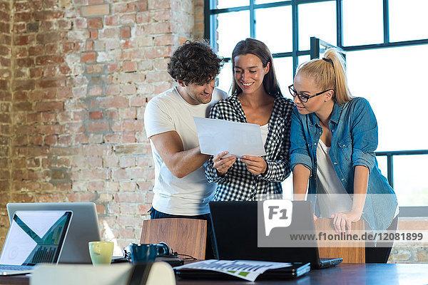 Junge Geschäftsleute  die im Büro stehen und den Businessplan für ihr Start-up-Unternehmen lesen.