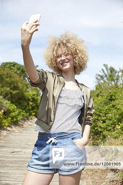 Porträt einer lächelnden jungen blonden Frau  die sich selbst mit dem Smartphone fotografiert.