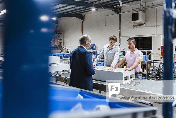 Geschäftsleute  die in der Werkstatt stehen und über Produktverbesserungen diskutieren.