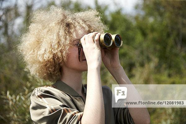 Junge Frau mit lockigem Haar  die durch ein altes Fernglas schaut.