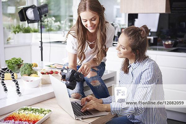 Zwei Lebensmittel-Blogger wählen Fotos auf Digitalkamera