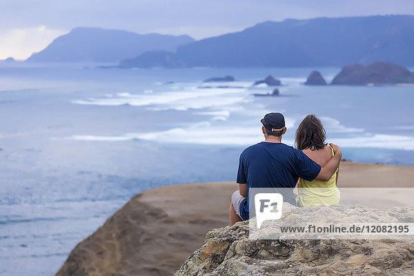 Indonesien  Lombok  Paar an der Küste sitzend mit Blick auf das Meer