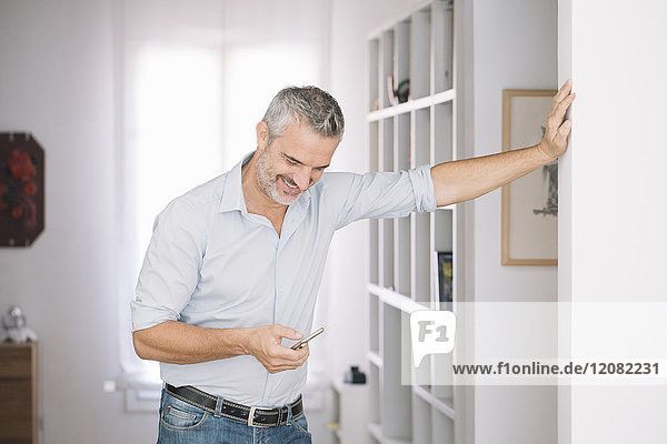 Smiling mature man using cell phone at home