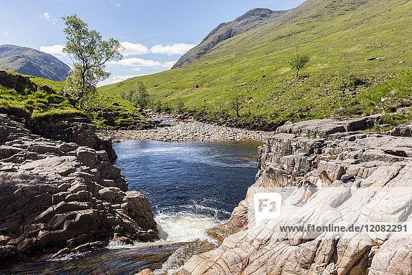 Großbritannien  Schottland  Schottische Highlands  Glen Etive mit River Etive und Glen Etive Falls  weibliche Touristenlektüre