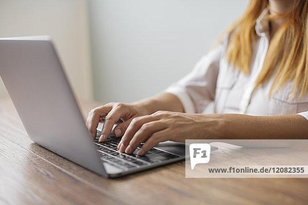 Hände der Geschäftsfrau bei der Arbeit am Laptop am Schreibtisch im Büro