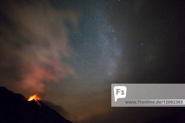 Italien  Äolische Inseln  Stromboli  Vulkanausbruch vor Nachthimmel und Milchstraßenhintergrund  Lavabomben