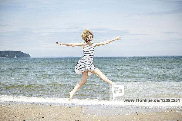 Fröhliche junge Frau  die vor dem Meer in die Luft springt.
