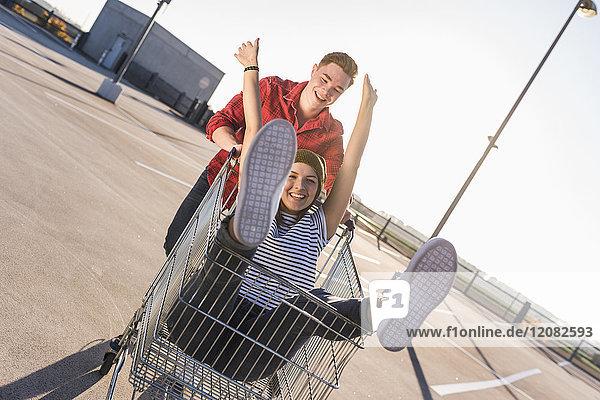 Verspieltes junges Paar mit Einkaufswagen auf Parkebene