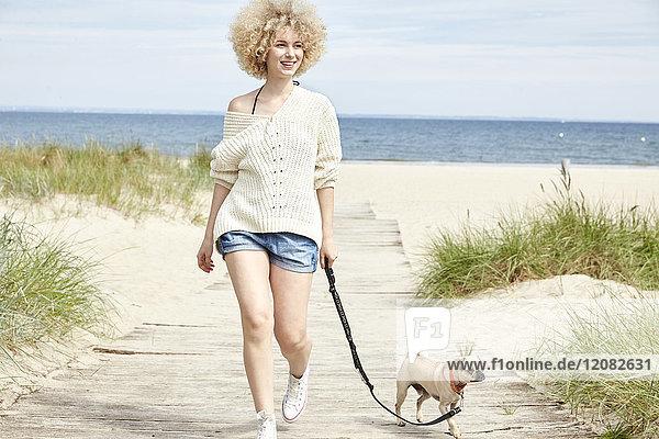Porträt einer lächelnden jungen Frau  die mit ihrem Hund am Strand spazieren geht.