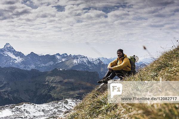 Deutschland  Bayern  Oberstdorf  lächelnder Wanderer sitzend in alpiner Landschaft