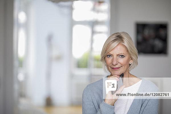Porträt einer älteren Frau mit Handy zu Hause