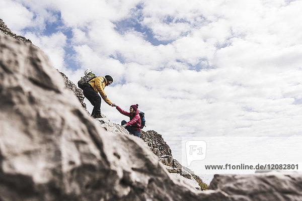 Deutschland  Bayern  Oberstdorf  Mann hilft Frau beim Klettern auf den Felsen