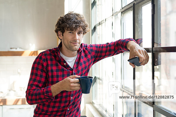 Young entrepreneur standing in company kitchen  drinking coffee