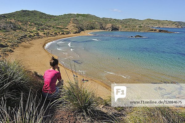 Young woman admiring the Cavalleria Beach at Cape Cavalleria on the North Coast of Menorca  Balearic Islands  Spain  Europe.