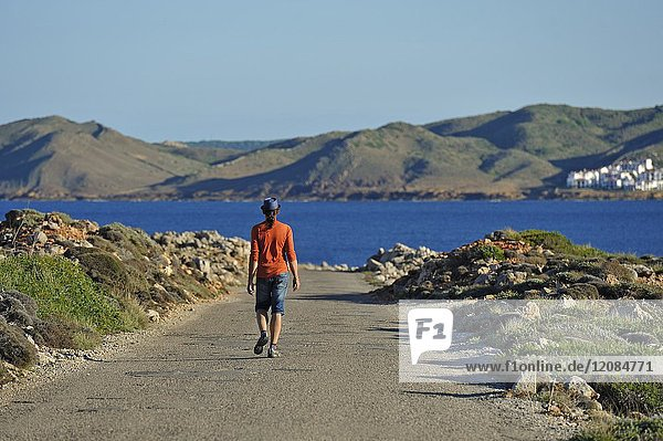 Man walking alone on the road coming from the Cape Cavalleria on the North Coast of Menorca  Balearic Islands  Spain  Europe.