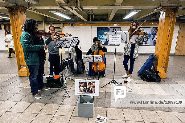 New York City  USA. African-American classical musicians playing inside an L Train subway station.