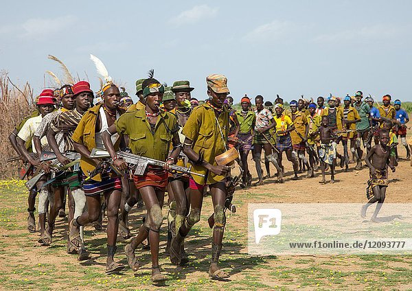 Men running in line with weapons during the proud ox ceremony in the Dassanech tribe  Turkana County  Omorate  Ethiopia.
