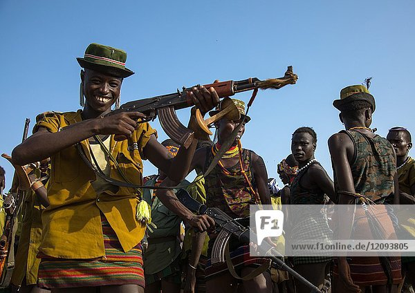 Man shooting with a kalashnikov during the proud ox ceremony in the Dassanech tribe  Omo valley  Omorate  Ethiopia.