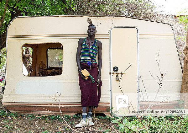 Sudanese Toposa tribe man refugee in front of an old abandonned caravan  Omo Valley  Kangate  Ethiopia.