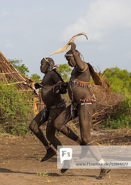 Bodi tribe fat men running during Kael ceremony  Omo valley  Hana Mursi  Ethiopia.