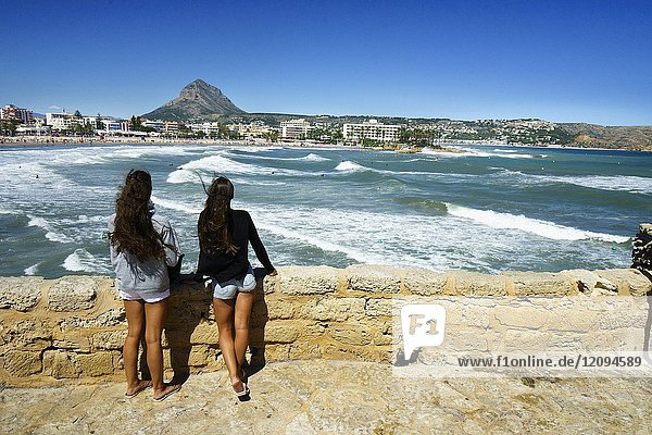 Two girls watching the waves on the beach of El Arenal in Javea  Alicante  Valencia  Spain  Europe