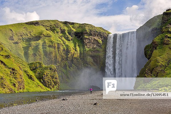 Woman staring at Skogafoss waterfall  Skogar  Sudurland  Iceland.