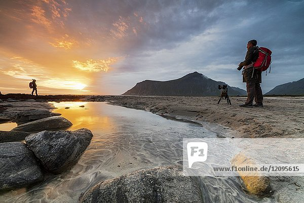 Midnight sun frames photographers in action on Skagsanden beach Ramberg Nordland county Lofoten Islands Northern Norway Europe.