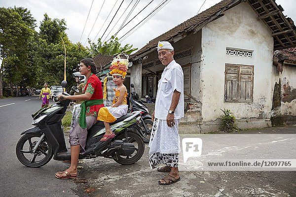 People wearing traditional Balinese clothing go to a local temple near Bugbug village. Karangasem Regency,  Bali,  Indonesia.