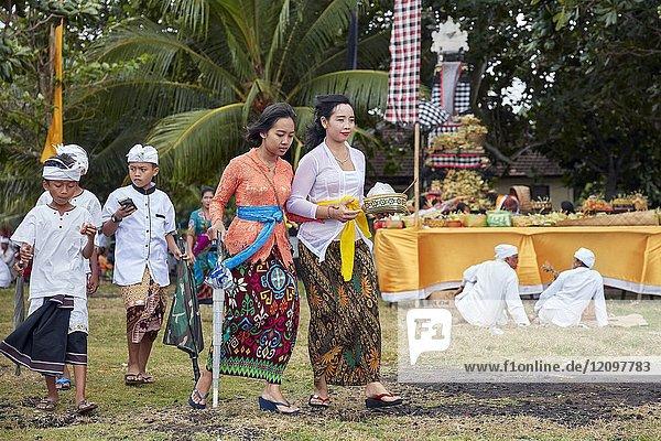 Women with children wearing traditional Balinese clothing go to a local temple. Sengkidu village near Candidasa  Karangasem Regency  Bali  Indonesia.