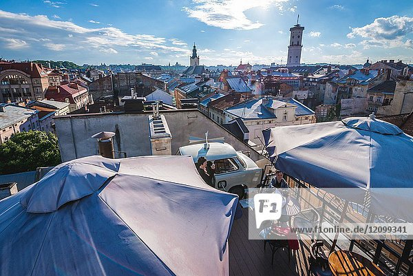 Roof of famous restaurant House of Legends with a Trabant car on the Old Town of Lviv city  largest city in western Ukraine. Town Hall tower on background.