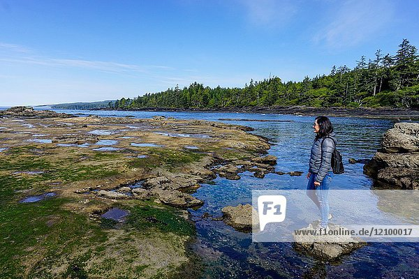 A latino woman admires Botanical Beach in Vancouver Island  BC.