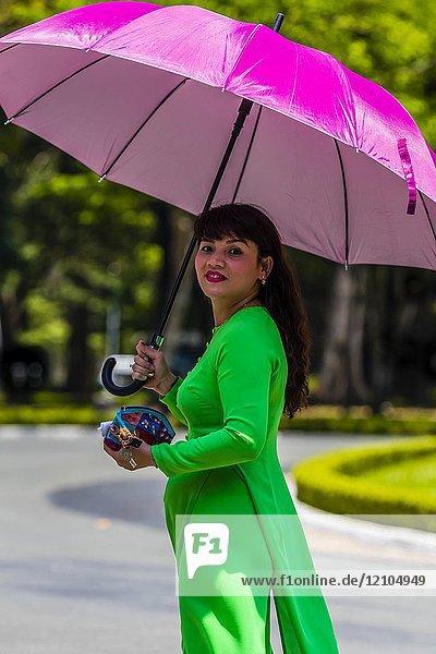 An elegant Vietnamese woman walks underneath her umbrella  Reunification Palace (formerly the Presidential Palace)  Ho Chi Minh City (Saigon)  Vietnam.