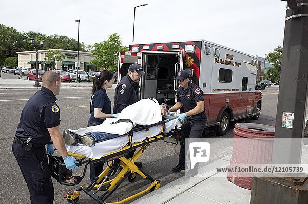 Paramedics rolling strapped down patient into emergency transport vehicle. St Paul Minnesota MN USA.