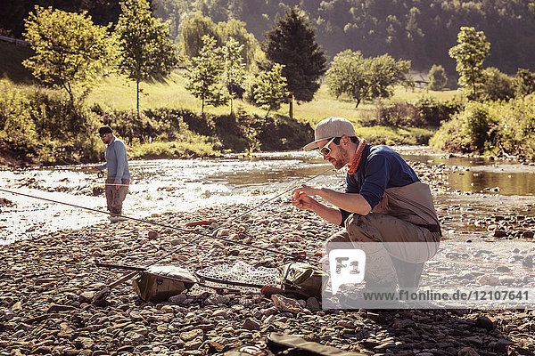 Young fisherman crouching with fishing rod by river  Mozirje  Brezovica  Slovenia