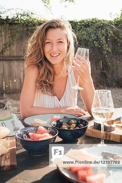 Porträt einer jungen Frau  im Freien  am Tisch sitzend  ein Weinglas haltend