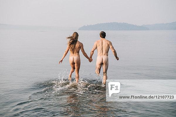 Rückansicht eines nackten Paares  das ins Wasser läuft
