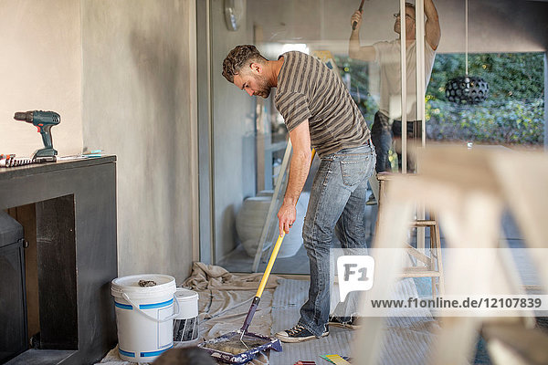 Two men in unfurnished home  decorating using paint roller